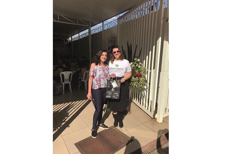 Clarissa Guedes, da loja Piuí Modas, entregando uma das premiações do bingo